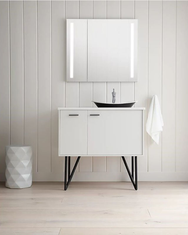mirror medicine cabinet positioned above a white vanity