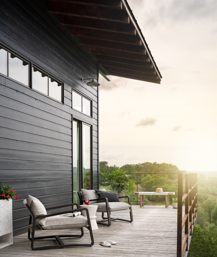 outdoor living space on a balcony with two chairs and setting sun